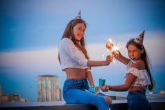 Dwa dziewczyny z Bengalia światłami w urodzinowych nakrętkach fotografia stock