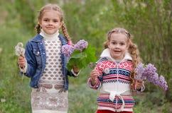 Dwa dziewczyny z dandelions i bzami Zdjęcia Royalty Free