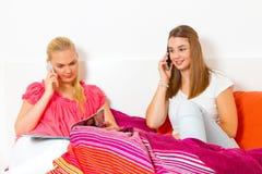 Dwa dziewczyny z mądrze telefonami Zdjęcia Royalty Free