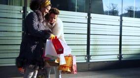 Dwa dziewczyny z pakunkami w ich r?kach dyskutuj? zakupy zdjęcie wideo