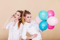 Dwa dziewczyny z telefonem komórkowym i balonami fotografia royalty free