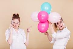 Dwa dziewczyny z telefonem komórkowym i balonami zdjęcie stock