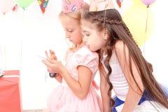 Dwa dziewczyny z telefonem komórkowym podczas przyjęcia urodzinowego fotografia royalty free
