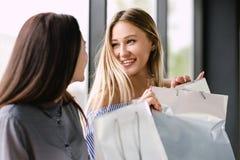Dwa dziewczyny z zakupy obsiadaniem na ławce w centrum handlowym obrazy royalty free