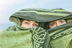 Dwa dziewczyny zakrywającej z koc Kobiety zakrywać z przesłoną i tajemniczym spojrzeniem obraz stock