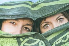 Dwa dziewczyny zakrywającej z koc Kobiety zakrywać z przesłoną i tajemniczym spojrzeniem zdjęcie royalty free