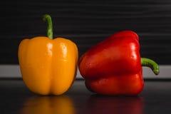 Dwa dzwonkowego pieprzu na nowożytnym kuchennym rozmytym tle fotografia stock