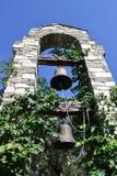 Dwa dzwonu wiesza na drewnianych promieniach w drylują łuk wśród zielonych rośliien Fotografia Stock