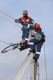 Dwa electrics pracuje na górze elektryczność pilonu Zdjęcie Stock