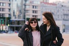 Dwa elegancki i piękni młoda dziewczyna przyjaciele jest ubranym przypadkowego przespacerowanie wokoło uśmiechu i miasta zdjęcia stock