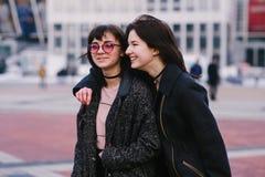 Dwa elegancki i piękni młoda dziewczyna przyjaciele jest ubranym przypadkowego przespacerowanie wokoło uśmiechu i miasta obrazy royalty free