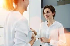 Dwa eleganckich kobiet przedsiębiorcy opowiada o coś podczas gdy stojący w nowożytnym biurowym wnętrzu, Obraz Royalty Free