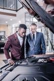 Dwa eleganckiego biznesmena jest ubranym biznesowego ubiór patrzeje samochód w salonie obrazy stock