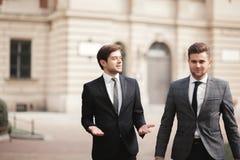 Dwa eleganckiego biznesmena mówi outdoors i ono uśmiecha się zdjęcie stock