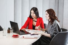Dwa eleganckiego dziewczyna projektanta pracuj? z laptopem i dokumentacj? przy projekta obsiadaniem przy biurkiem projektuj?cy zdjęcie stock