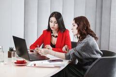 Dwa eleganckiego dziewczyna projektanta pracuj? z laptopem i dokumentacj? przy projekta obsiadaniem przy biurkiem projektuj?cy fotografia royalty free