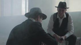 Dwa eleganckiego m??czyzny siedzi w zaniechanym budynku dyskutuje biznes w kapeluszach Mafijni faceci spotkania w pustym zdjęcie wideo