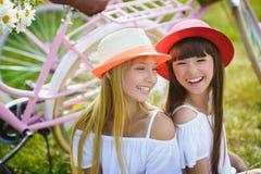 Dwa eleganckiej nastoletniej dziewczyny na bicyklu Najlepsi przyjaciele cieszy się dzień na rowerze Fotografia Royalty Free
