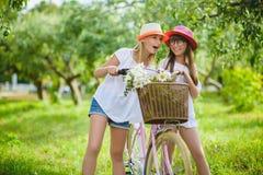 Dwa eleganckiej nastoletniej dziewczyny na bicyklu Najlepsi przyjaciele cieszy się dzień na rowerze Obrazy Royalty Free
