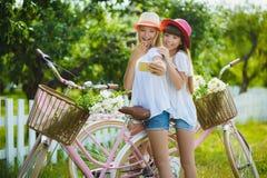 Dwa eleganckiej nastoletniej dziewczyny na bicyklu Najlepsi przyjaciele cieszy się dzień na rowerze Fotografia Stock
