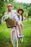 Dwa eleganckiej nastoletniej dziewczyny na bicyklu Najlepsi przyjaciele cieszy się dzień na rowerze Zdjęcia Royalty Free