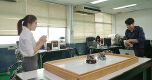 Dwa elektronika inżyniera kontrola i programowania roboty bawić się piłkę nożną zbiory