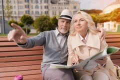 Dwa emeryta siedzą na ławce i studiują mapę miasto Zdjęcia Royalty Free