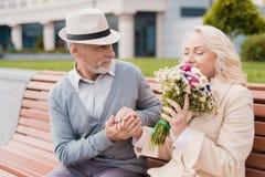 Dwa emeryta siedzą na ławce w alei Starzejący się mężczyzna dać kobiecie kwiaty Trzyma jej rękę Zdjęcie Royalty Free
