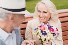 Dwa emeryta siedzą na ławce w alei Starzejący się mężczyzna dać kobiecie kwiaty Trzyma jej rękę Zdjęcia Royalty Free