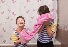 Dwa emocjonalnego brata bawić się z ręcznikiem w łazience Zdjęcie Stock