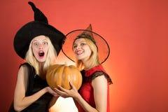 Dwa emocjonalnej m?odej kobiety w Halloween kostiumach na przyj?ciu z bani? Najlepszy przyjaciel dziewczyny ?wi?tuj? dzi?kczynien zdjęcia stock