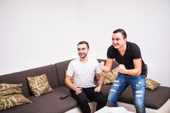Dwa excited piłki nożnej fan siedzą na kanapie i oglądają faworyta drużynowego cel przy tv Fotografia Royalty Free