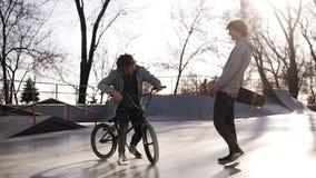 Dwa faceci, przyjaciele i bmx jeźdza spotkania outdoors aktywnych, - deskorolkarz w miasto łyżwy parku Przyjaciele komunikują w zbiory wideo