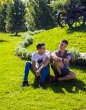 Dwa faceta siedzą na gazonie i opowiadali coś obraz royalty free