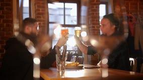 Dwa faceta siedzi przy stołem w restauracji Para szkła w przedpolu Otuchy, zwolnione tempo zdjęcie wideo