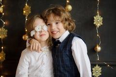 Dwa festively ubierającego dziecka fotografującego dla kartki bożonarodzeniowa zdjęcia stock