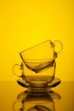 Dwa filiżanek koloru żółtego przejrzysty szklany tło Zdjęcie Royalty Free