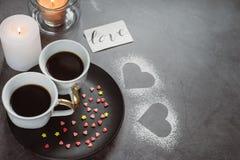Dwa filiżanka kawy, świeczka i serca na ciemnym tle, Dzień wszystkie kochankowie zdjęcia royalty free