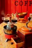 Dwa filiżanki świeżej warzącej kawy espresso na piecowym odgórnym retro mini kawowym producencie z ostrzarzem w przedpolu obrazy stock