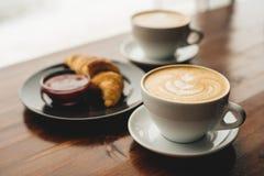 Dwa filiżanki cappuccino i croissant zdjęcie royalty free