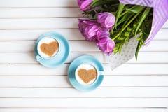 Dwa filiżanki cappuccino z kierowym kształtnym symbolem i purpurowych tulipany na drewnianym tle obrazy stock