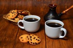 Dwa filiżanki czarna kawa z crispy amerykańskimi ciastkami i glinianym tureckim kawowym producentem na ciemnego brązu drewnianym  fotografia stock