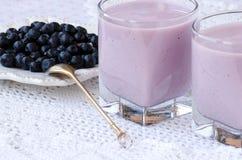 Dwa filiżanki czarnej jagody łyżka na stole i jogurt Zdjęcie Royalty Free