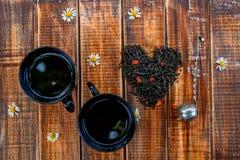 Dwa filiżanki herbaciany pobliski suszy liście czerń robi w sercu na drewnianym tło rocznika durszlaku Pojęcie Odgórny widok zbli Zdjęcia Royalty Free