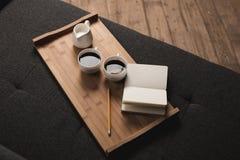 Dwa filiżanki kawy, dzbanek mleko i notatnik z ołówkiem na drewnianej tacy, fotografia stock