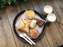 Dwa filiżanki kawy i talerz z chlebowymi rolkami i tortami Drewniany tło zdjęcie ruchomej Zdjęcia Royalty Free