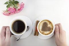 Dwa filiżanki kawy na białym tle z rękami, róż ręki obrazy stock
