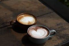 Dwa filiżanki latte kawa z kierowym kształt piany mlekiem na nieociosanym drewnianym stole dla datować pary pojęcie z kopii przes fotografia stock
