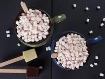 Dwa filiżanki z gorącą czekoladą i minymi marshmallows na ciemnego brązu tle, zdjęcia stock