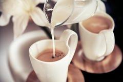 Dwa filiżanki kawy z dekoracją i nalewającym mlekiem Obrazy Royalty Free